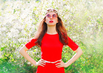 Fashion portrait beautiful hippie young woman over flowering garden background