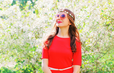 Fashion pretty smiling woman looks with hope up over spring flowering garden background