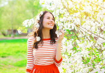 Happy smiling young woman with spring flowers at garden