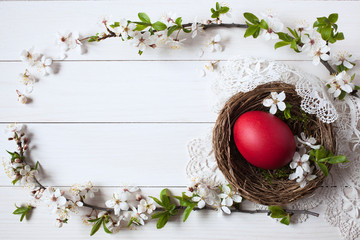 Easter background with a nest, egg and branch with flowers