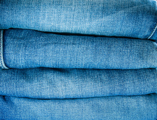 Pile of blue jeans, fabric texture