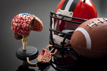 Brain damage and sports injury concept with damaged brain model, american football helmet and a ball, illustrating CTE (Chronic traumatic encephalopathy) a syndrome caused by repeated concussion