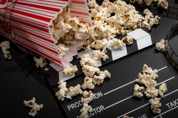Movies and entertainment concept with dropped box of popcorn on film strip and clapper board and pop corn scattered everywhere