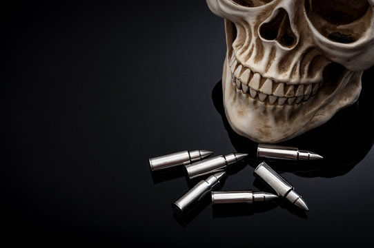 Gun violence and death concept with human skull and scattered bullets isolated on black background and copy space