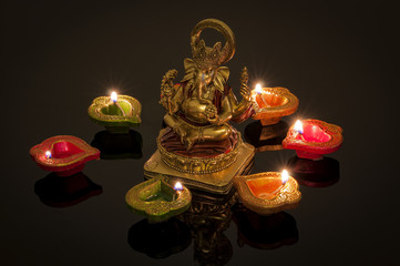 Hindu religion and Indian celebration of Diwali festival concept with diya lamps and candles around the Lord Ganesh. Ganesha is the patron of arts and sciences and the deva of intellect and wisdom