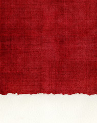 Deckled Paper Edge on Red Cloth. A section of deckled edge paper on a textured, red cloth background.