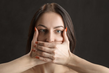 woman cover her mouth on black background