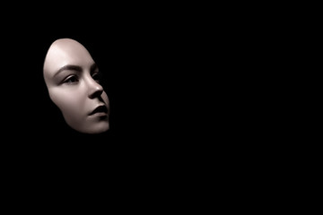 sad female face mask on black background with copy space