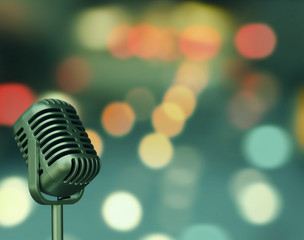 Vintage microphone with blurred bight light background and soft focus