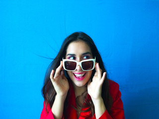 Shot portrait of surprised smiling woman whit long brunette hair and in white sunglasses in vibrant blue background with red clothes