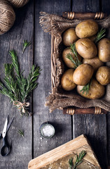 Potato with rosemary on rustic background