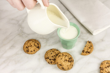Milk poured into glass, with chocolate chips cookies
