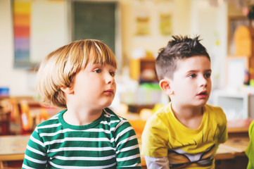 Two concentrated 4-5 year old boys in classroom