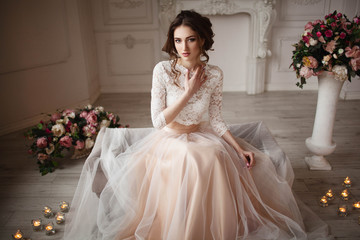 Girl with make-up in a wedding dress sits in a beautiful room