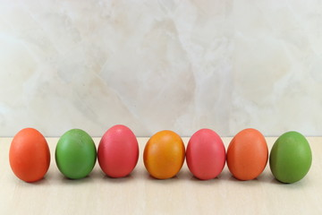 Row of colorful easter eggs on marble with copy space background.