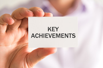 Businessman holding a card with KEY ACHIEVEMENTS message