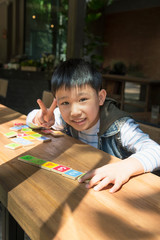 Asian Boy Happy With Wooden Toy Plate Numbers On Wood Table.