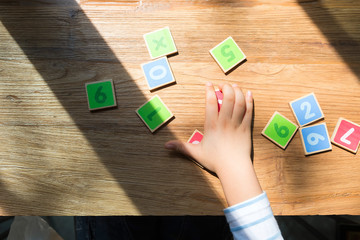 Child Hand With Wooden Toy Plate Numbers On Wood Table.