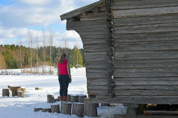 Woman standing on log and watching winter landscape on countryside