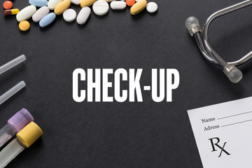 CHECK-UP written on black background with medication