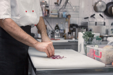 chef cutting onions, cutting board, closeup