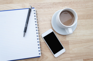 coffee with notebook,smartphone on wooden table, view from above