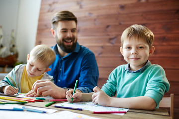 Waist-up portrait of family having fun together: two funny little brothers sitting at wooden table and coloring pictures while their dad savoring the moment