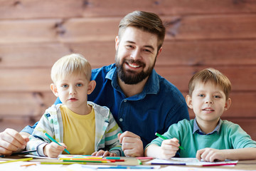 Portrait of happy loving family: two brothers drawing with pencils and felt-tip pens and their father looking at camera with wide smile