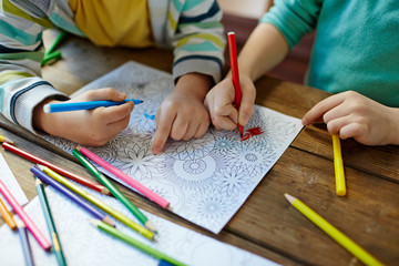 Close-up shot of two pairs of little hands coloring mandala with felt-tip pens, pencils of...