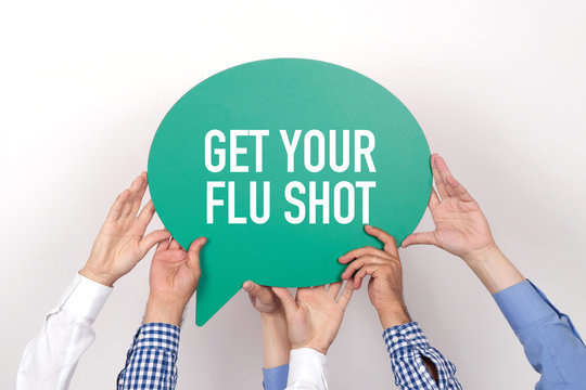 Group of people holding the GET YOUR FLU SHOT written speech bubble