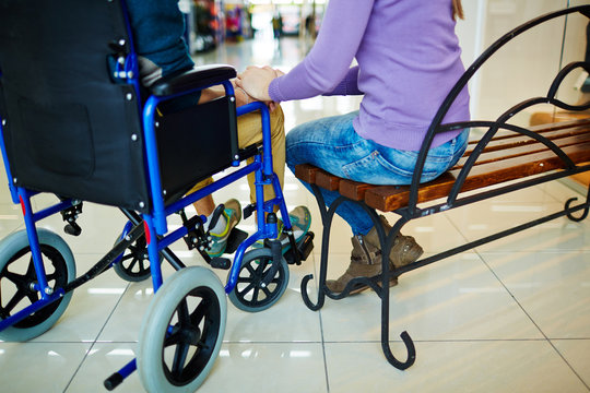 Rear view of girl on bench and disabled guy in wheelchair holding hands while having date in shopping mall
