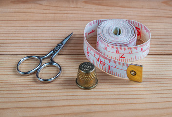 Scissors, thimble, tape measure in the background of village