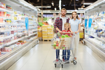 Full-length portrait of confident young family with little son standing in supermarket and holding full shopping cart