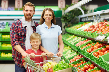Cheerful family of three with full shopping trolley posing for camera in fruit and vegetable department of supermarket