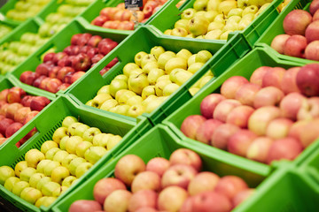 Fresh tasty green, yellow and red apples lying in green plastic boxes in supermarket