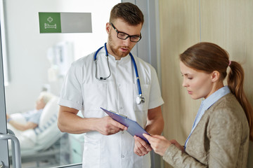 Young doctor showing patients medical report to upset young woman waiting outside closed ward, explaining the illness case of her elderly relative lying on bed inside the room