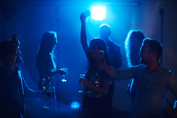 Students relaxing in fashionable night club, dancing with champagne glasses and chatting in the dark