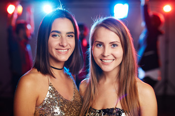 Portrait of two young pretty girls in shining tops looking at camera with bright toothy smiles while hanging out in nightclub