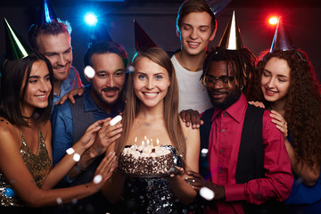 Group photo of dressed-up young people celebrating birthday of their female friend standing in the middle with cake and smiling happily