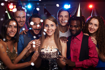 Young pretty girl celebrating birthday among close friends in night club, holding cake with candles and smiling at camera joyfully