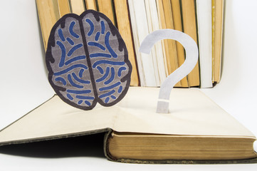 Paper brain silhouette and question mark is over old open medical book. Photo to refer issues and questions in study of brain, as well as difficulties in diagnosis in neurology and neuroscience