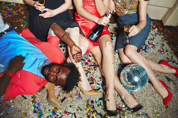 Waist-up portrait of calm African American in pink jacket lying on floor next to three pairs of female legs, unrecognizable young women sitting on carpet and drinking champagne from flutes and bottle