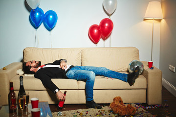 Smiling middle-aged man lying on couch and drinking beer from bottle in messy living room, empty alcohol bottles and plastic cups standing everywhere