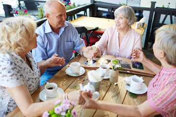 Cheerful senior people sitting in outdoor cafe and holding hands, worn-out photo book lying on table