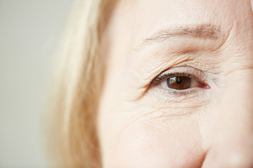 Sad eye of elderly blond-haired woman looking at camera, close-up shot