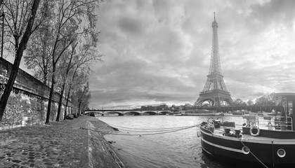 Beautiful panoramic view of the Eiffel Tower and Jena bridge from the river Seine embankment. Dramatic cloudscape. Traditional citycape in backlit morning sunbeam. BW photography. Paris, France.