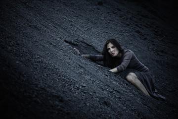 Beautiful sad girl on a mound of coal