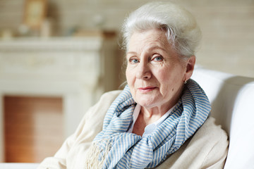 Portrait of elegant elderly woman with natural make-up and striped scarf sitting in armchair and looking at camera thoughtfully
