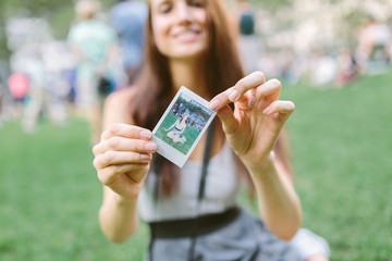 Girl holds instant photo in Bryant Park, Manhattan New York, USA