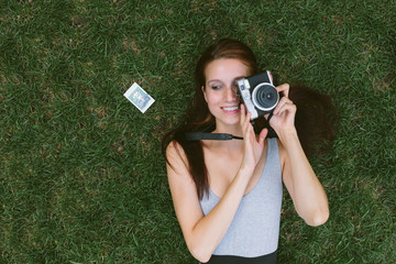 Young woman lying on the grass taking pictures with a vintage camera